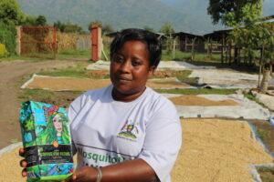 Frau aus Uganda hält eine Kaffeepackung in der Hand.